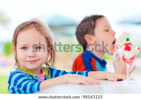 Two little adorable kids eating ice cream - stock photo