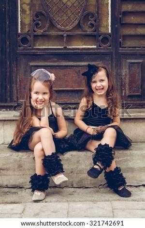 Two little ballerinas in black tutu sitting on staris - stock photo