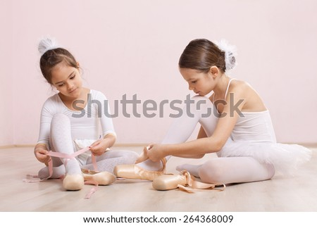 Two little ballerinas sitting on the floor and adjusting their ballet slippers. They are very cute - stock photo