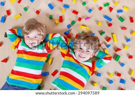 Two little blond children playing with lots of colorful wooden blocks indoor. Active kid boy wearing colorful shirt and having fun with building and creating.