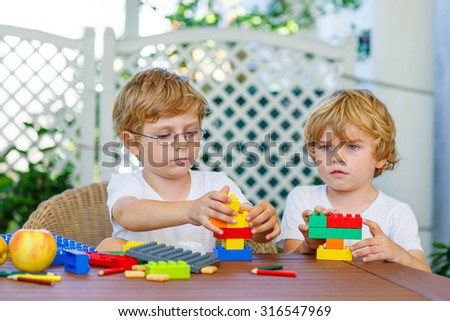 Two little blond friends playing with lots of colorful plastic blocks indoor. Active kid boys, siblings having fun with building and creating together. - stock photo