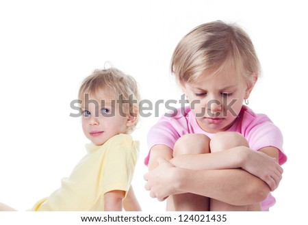two little blond girls in quarrel on white background