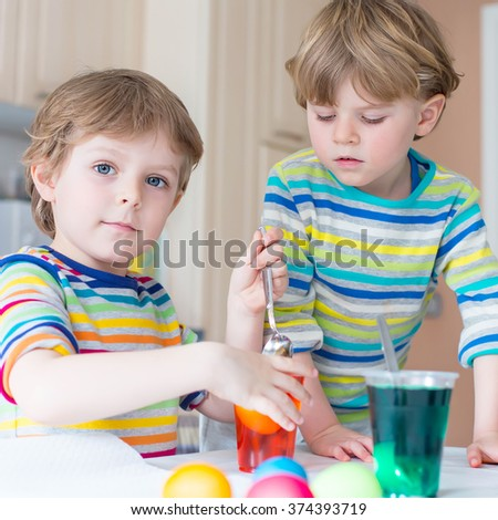Two little blond kid boys, brothers coloring eggs for Easter holiday in domestic kitchen, indoors. Children having fun and celebrating feast.