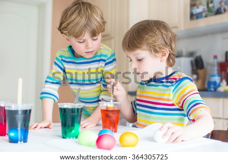 Two little blond kid boys coloring eggs for Easter holiday in domestic kitchen, indoors. Children having fun and celebrating feast.