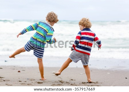 Two little blond kid boys having fun on lonely ocean beach. Friends, Children playing and running on stormy windy bad weather day. - stock photo