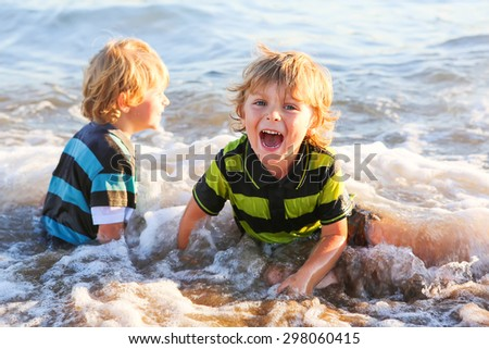 Two little blond kid boys having fun with waves and water on a ocean beach at sunset. Happy siblings. - stock photo
