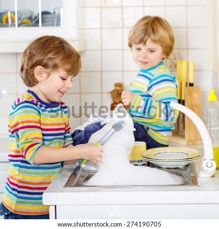 Two little blond kid boys washing dishes in domestic kitchen. Children having fun with helping with housework. Indoors, siblings in colorful clothes. Selective focus