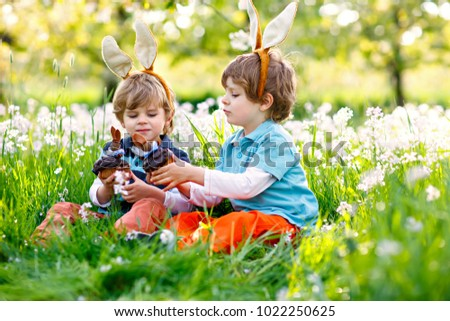 Two little boy friends in Easter bunny ears eating chocolate cakes and muffins