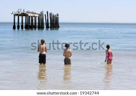 Two little boys and a girl, standing in the sea looking at a bird colony on an abandoned pier.