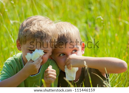 Two little boys are blowing their noses on green meadow - stock photo