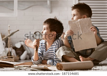 Two little boys are studying old travel card in my room - stock photo