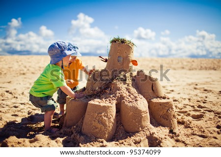 Two little boys building large sandcastle on the beach - stock photo