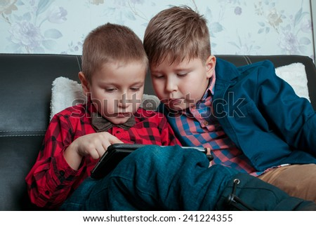 two little boys businessman with tablet isolated on a dark background - stock photo
