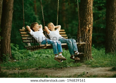 two little boys dreaming on swing - stock photo