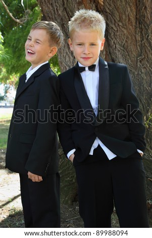 two little boys dressed in tuxedo standing near tree at sunny day outdoor; focus on boy on right - stock photo