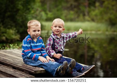 Two little boys fan on the bridge of the lake - stock photo