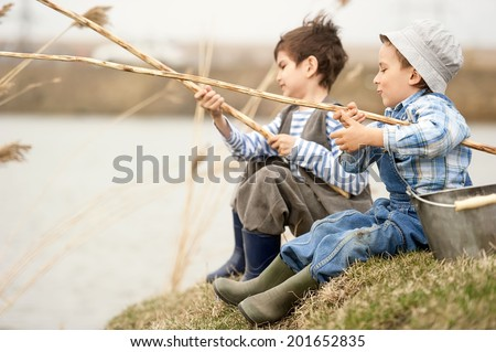 Two little boys fishing on the river   - stock photo