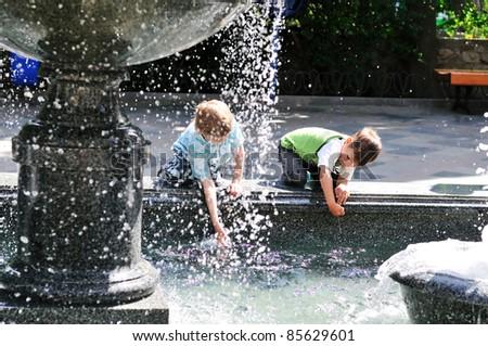 two little boys having fun near waterworks - stock photo