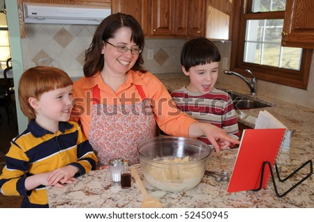 Two little boys help their mother bake chocolate chip cookies - stock photo