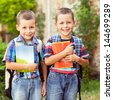 Two little boys holding notebooks while posing in front of their school. - stock photo