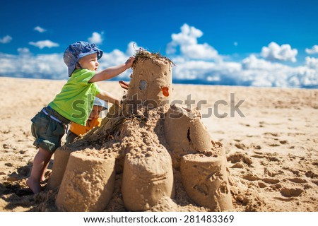 Two little boys in colorful t-shirts building large sandcastle on the beach - stock photo