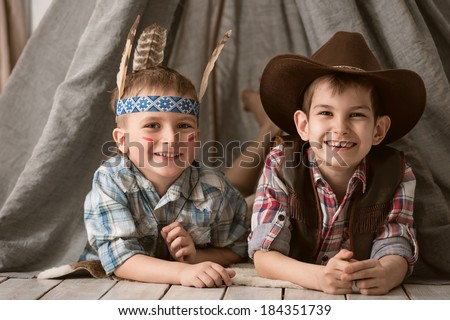 Two little boys in the image of cowboys and Indians play in his room - stock photo