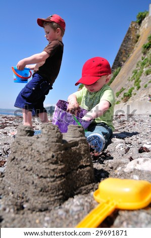 two little boys, making sandcastles on the beach. - stock photo