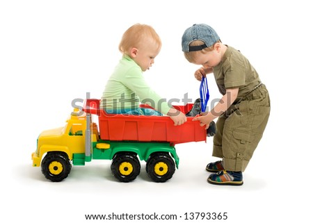 Two little boys play with toy truck. One boy sit on the car and second boy repair the car's body - stock photo
