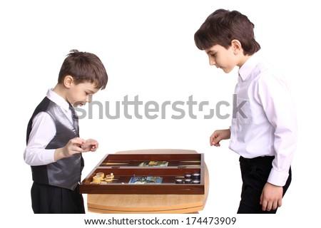 two little boys playing backgammon in studio - stock photo