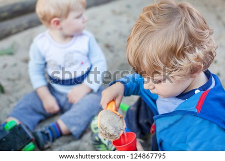 Two little boys playing with sand in summer on playground, outdoors
