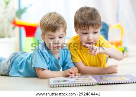 two little boys read together in nursery - stock photo