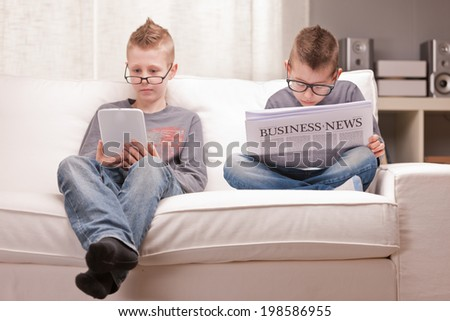 two little boys reading on newspapers or digital devices - stock photo