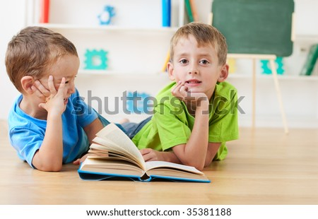 two little boys reading together on the floor - stock photo