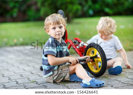 Two little boys, siblings, repairing bicycle outdoors