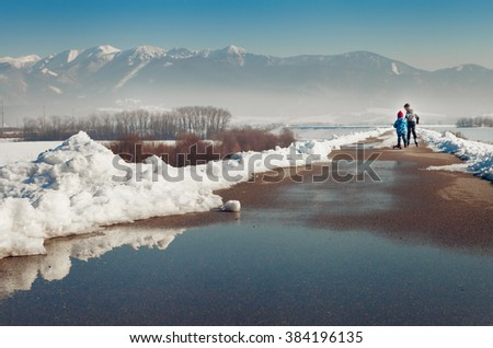 Two little boys skate together on the asphalt clear out from snow - stock photo