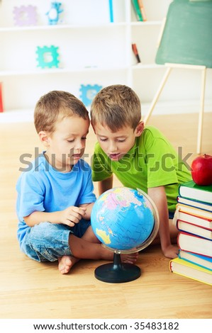 two little boys studying geography together - stock photo