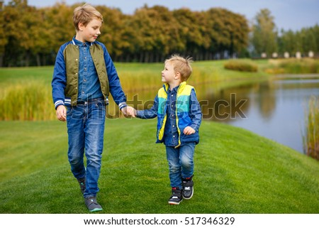 Two little boys walking in the park. One has ten years, another four years. Happy brothers. The beautiful nature around. They hold hands and look at each other.