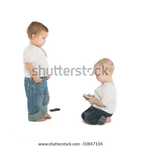 Two little boys with cellphones, white background - stock photo