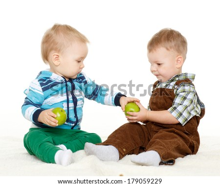 Two little boys with fresh apples sit on a white background. Healthy food.