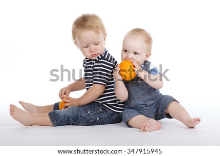 two little boys with orange on white