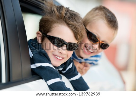 Two little boys with shades playing inside the car - stock photo