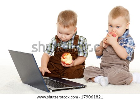 Two little boys with  with notebook and fresh apples sit on a floor on a white background. - stock photo