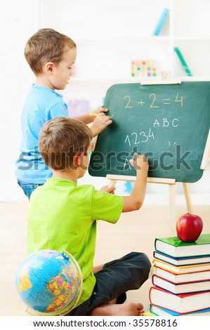 two little boys writing  together on chalkboard - stock photo