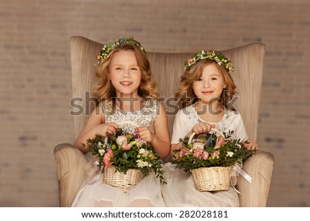 two little bridesmaid sitting in a chair with bouquets - stock photo