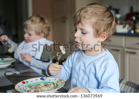 Two little brother boys eating pasta meal in home kitchen. Selective focus