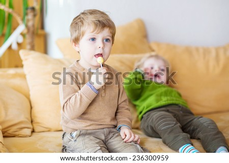 Two little brother boys watching tv and eating candy indoor. Selective focus on child on foreground. Kids fun at home. - stock photo