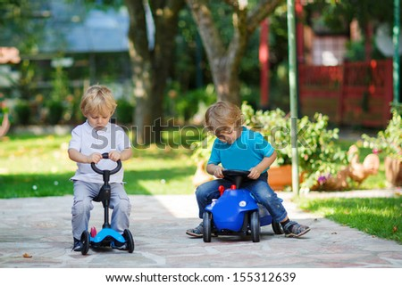 Two little brother toddlers playing with toy car and bicycle in summer garden - stock photo