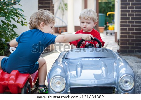 Two little brother toddlers playing with toy car in summer garden