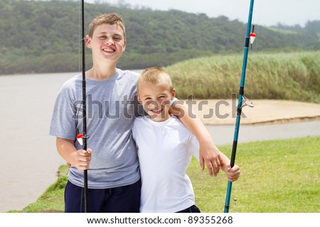 two little brothers fishing by the lake - stock photo