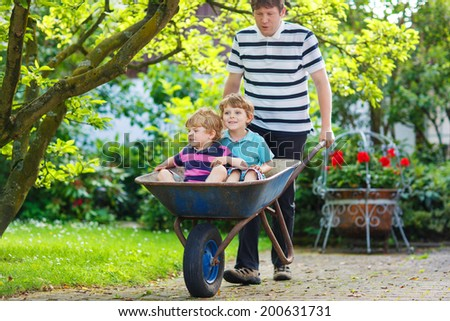 Two little brothers having fun in a wheelbarrow pushing by father in summer garden - stock photo